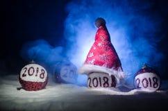 Rode Kerstmisballen met het aantal van 2018 en de hoed van de Kerstman op natuurlijke sneeuwachtergrond Gelukkig Nieuwjaar 2018 c Stock Foto
