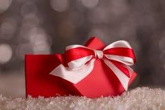 Rode Kerstmisdoos met boog in de sneeuw op grijze achtergrond met bokeheffect royalty-vrije stock fotografie