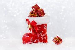 Rode Kerstmiskous met giften, santa` s laars in sneeuw, bokeh en snowflackes royalty-vrije stock afbeeldingen