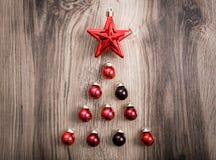 Rode Kerstmisornamenten in de vorm van een Kerstmisboom op een rustieke houten achtergrond Vrolijke Kerstkaart Gelukkig Nieuwjaar Royalty-vrije Stock Foto's