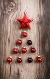 Rode Kerstmisornamenten in de vorm van een Kerstmisboom op een rustieke houten achtergrond Vrolijke Kerstkaart Gelukkig Nieuwjaar Stock Afbeelding
