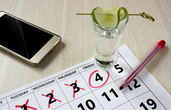 Rode kleur die op de kalender bij vrijdag met schot van tequila met een plak van kalk en telefoon schrijven Royalty-vrije Stock Foto's