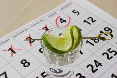Rode kleur die op de kalender bij vrijdag met schot van tequila met een plak van kalk schrijven Stock Foto's