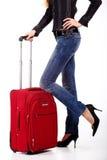 Rode koffer en van vrouwen benen Royalty-vrije Stock Afbeeldingen