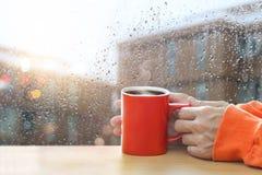 Rode koffiekoppen in handen op een vensterglas van regendruppels Stock Foto