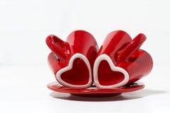 rode koffiekoppen met harten op witte achtergrond, close-up Stock Afbeelding