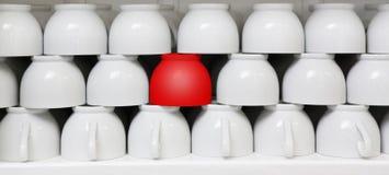 Rode kop amid witte koffiekoppen Stock Afbeeldingen