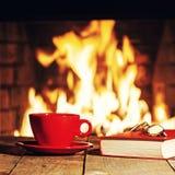 Rode kop, glazen en oud boek dichtbij open haard op houten lijst stock fotografie