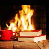 Rode kop thee of koffie en oude boeken dichtbij open haard N royalty-vrije stock fotografie
