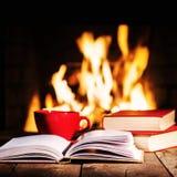 Rode kop van koffie of thee en oude boeken op houten lijst dichtbij open haard Stock Afbeeldingen