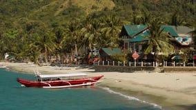 Rode kraanbalkboot op schoon wit zandstrand met een mooi huis, Filippijnen stock video
