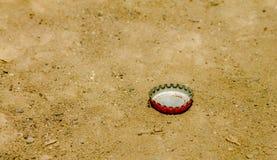 Rode kroonkurk op vuil Royalty-vrije Stock Afbeeldingen