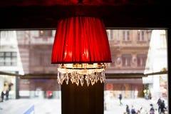Rode kroonluchter over het venster met een mening van de stad Stock Fotografie