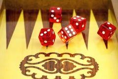 Rode kubussen tegen de achtergrond van een raad voor het dobbelen royalty-vrije stock foto