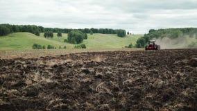 Rode landbouwbedrijftractor die een gebied ploegen stock video