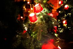 Rode lantaarns op een tak van een Kerstboom op een rode bakstenen muurachtergrond Stock Fotografie