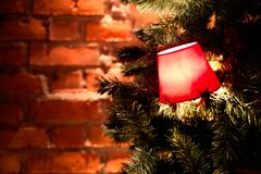 Rode lantaarns op een tak van een Kerstboom op een rode bakstenen muurachtergrond Stock Foto