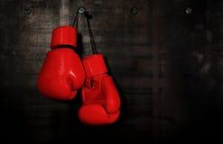 Rode leer bokshandschoenen die op zwarte muur hangen royalty-vrije stock afbeeldingen