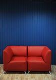 Rode leerbank op een achtergrond van blauwe muren Textuur voor het ontwerp Royalty-vrije Stock Afbeeldingen