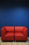 Rode leerbank op een achtergrond van blauwe muren Textuur voor het ontwerp Royalty-vrije Stock Afbeelding