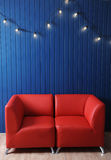 Rode leerbank op een achtergrond van blauwe muur met retro slinger van gloeilampen Textuur voor het ontwerp Royalty-vrije Stock Foto's