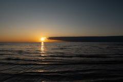 Rode levendige zonsondergang bij de Oostzee met spiegel zoals water - Geribbeld zand en golven - Veczemju Klintis, Letland - Apri stock foto