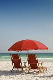 Rode Ligstoelen en Paraplu Stock Fotografie