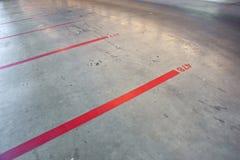 Rode lijnen en aantallen in lege parkerengarage Stock Foto's