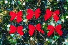 Rode linten tussen Kerstmislichten en kleurrijke decoratie i stock fotografie