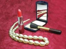 Rode lippenstiftpoeder en parels royalty-vrije stock afbeelding