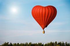 Rode luchtballon in de vorm van een hart die in blauwe hemel vliegen royalty-vrije stock afbeeldingen
