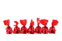 Rode luxesnoepjes in een rij die op wit wordt geïsoleerdw Royalty-vrije Stock Afbeeldingen