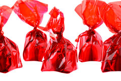 Rode luxesnoepjes in zigzagrij die op wit wordt geïsoleerdr Stock Foto's