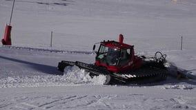 Rode machine voor het ski?en hellingsvoorbereidingen in Oostenrijkse Alpen bij achtergrond van bergen stock video
