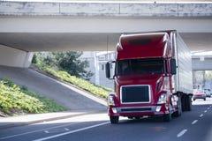 Rode moderne semi vrachtwagen met adelborstaanhangwagen onder brug Royalty-vrije Stock Foto