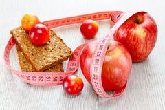 Rode mooie appelen en pruimenmeterband Royalty-vrije Stock Afbeeldingen