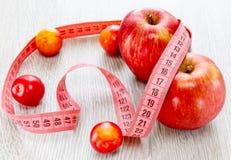 Rode mooie appelen en pruimenmeterband Stock Foto's