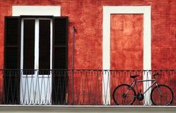 Rode muur en fiets, Italiaans balkon Stock Foto's