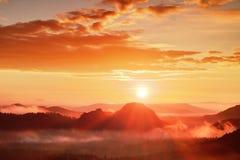 Rode nevelige dageraad Mistige de herfstochtend in mooie heuvels De pieken van heuvels plakken uit van rijke kleurrijke wolken Royalty-vrije Stock Afbeeldingen