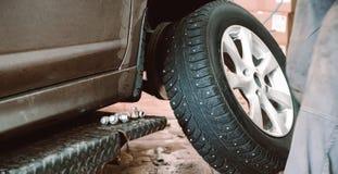 Rode o equilíbrio ou o reparo e mude o pneu de carro na auto garagem do serviço ou a oficina pelo mecânico fotos de stock
