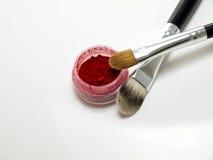 Rode oogschaduw en kosmetische borstels Stock Fotografie
