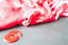 Rode oorringen en rood sjaalclose-up op steenachtergrond Stock Foto