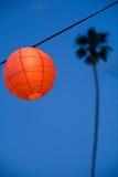 Rode/oranje lantaarn met palm op achtergrond Stock Foto