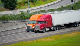 Rode oranje semi vrachtwagensaanhangwagens die wegweg samen drijven Royalty-vrije Stock Foto