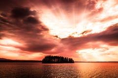 Rode oranje zonsondergang over het meer met een klein eiland royalty-vrije stock fotografie