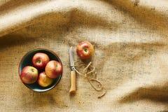 Rode organische appelen in kom met mes op stof Royalty-vrije Stock Afbeelding