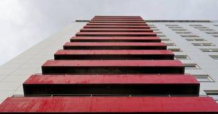 Rode oude doorstane balkons op de voorgevel van een lelijk high-rise gebouw Stock Foto
