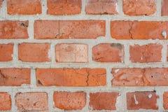 Rode oude langzaam verdwenen bakstenen muurachtergrond met barsten en gebreken stock foto's