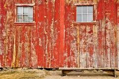 Rode oude schuurvensters en eenzame bank Royalty-vrije Stock Afbeeldingen