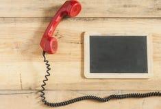 Rode ouderwetse telefoonontvanger op houten lijst Stock Foto